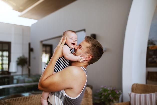 Padre caucasico bello felice che abbraccia il suo figlio amorevole di 6 mesi mentre levandosi in piedi all'interno. il bambino sta ridendo e abbracciando il padre.
