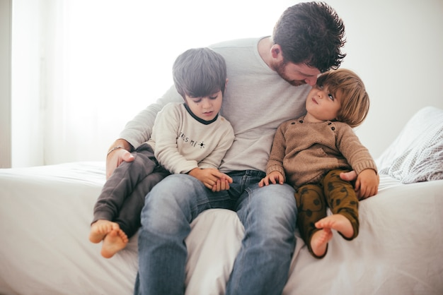 Padre che abbraccia figli maschi