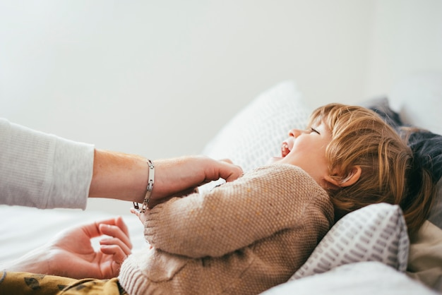 Padre che gioca con il bambino sul letto