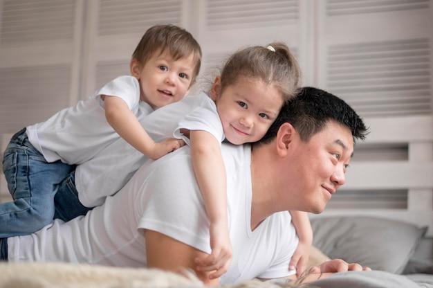 Padre che gioca con la figlia e il figlio