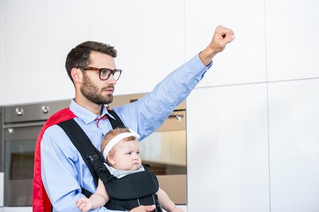 Padre che indossa la figlia di trasporto costume da supereroe