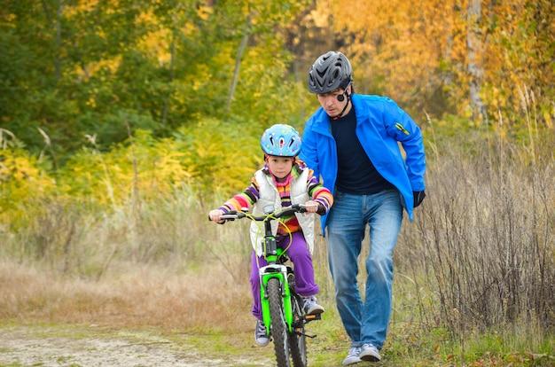 Padre che insegna al bambino a guidare la bici in autunno parco