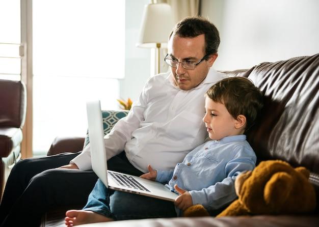 Padre che insegna al figlio come usare il portatile