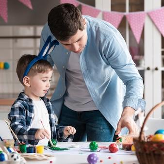 Padre che insegna al ragazzino come dipingere le uova di pasqua