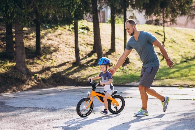 Padre che insegna al suo piccolo figlio ad andare in bicicletta