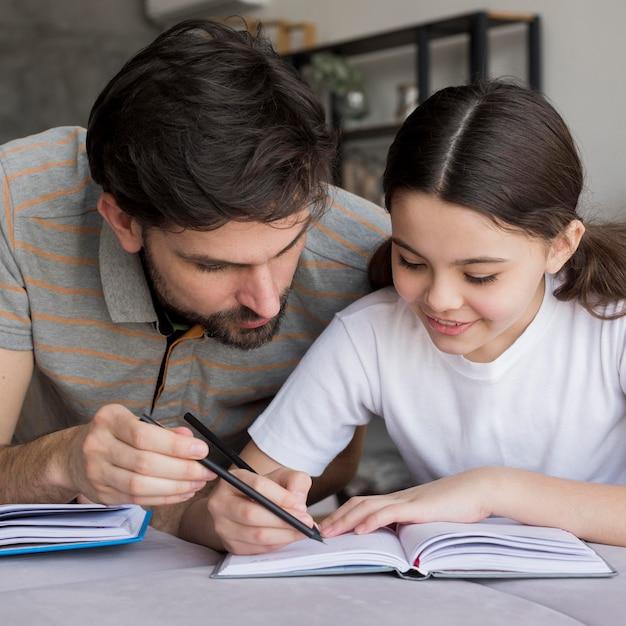 Padre che insegna alla ragazza a scrivere