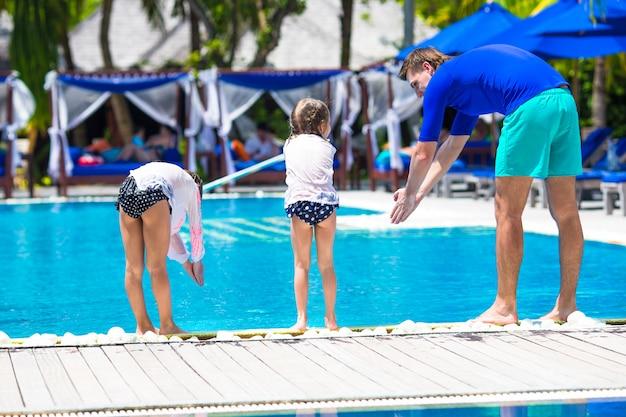 Padre che insegna alle sue figlie a tuffarsi in piscina in un resort tropicale