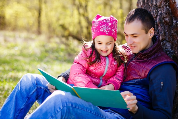 Padre che legge il libro alla sua giovane figlia sotto l'albero nel parco con sua moglie.