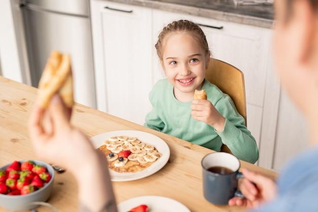 Padre che mangia crepe e gode della colazione con la figlia, bella ragazza sorridente che ascolta il padre e mangia crepe fatte in casa