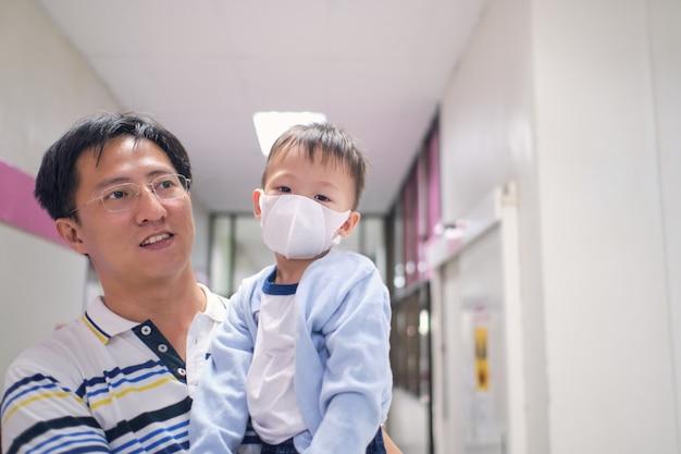 Padre che tiene carino asiatico 3 anni bambino ragazzo bambino che indossa maschera medica protettiva, genitore e bambino malato