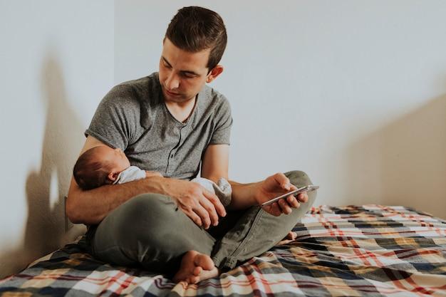 Padre che tiene il suo bambino mentre usa il suo telefono