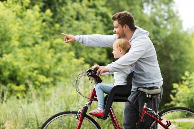 Padre che tiene la figlia sulla bici