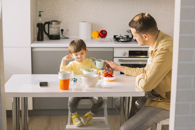 Padre che tiene la tazza per suo figlio da bere