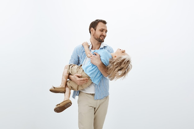 Padre che tiene prezioso tesoro nelle mani. ritratto di simpatico papà europeo felice in abito casual che porta il figlio tra le braccia, sorridente e guardando la faccia del ragazzo