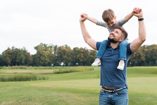 Padre che tiene suo figlio sulle spalle