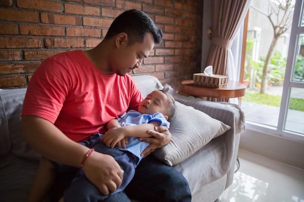 Padre che trasporta suo figlio addormentato