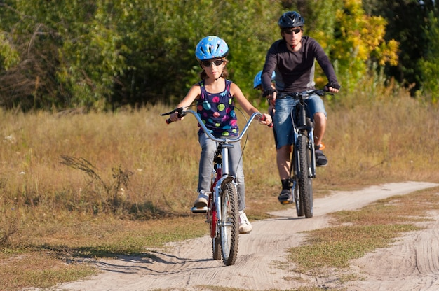 Padre con bambini andare in bicicletta all'aperto