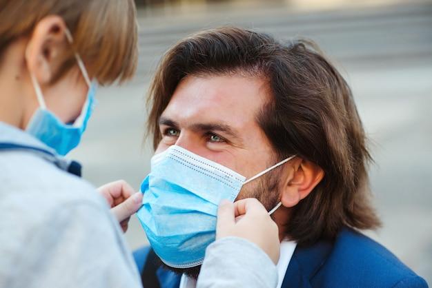 Padre con bambino in mascherina medica in via della città.