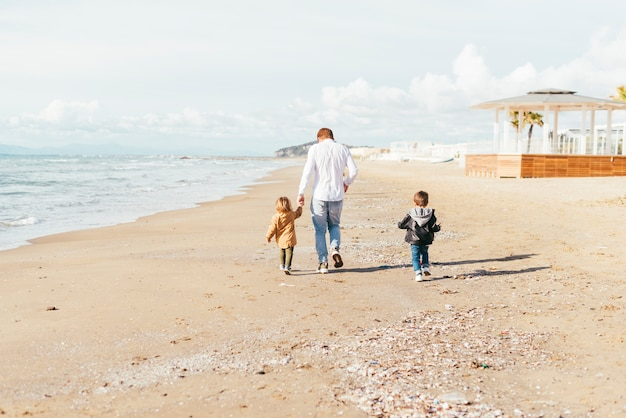 Padre con figli che passeggiano lungo la spiaggia