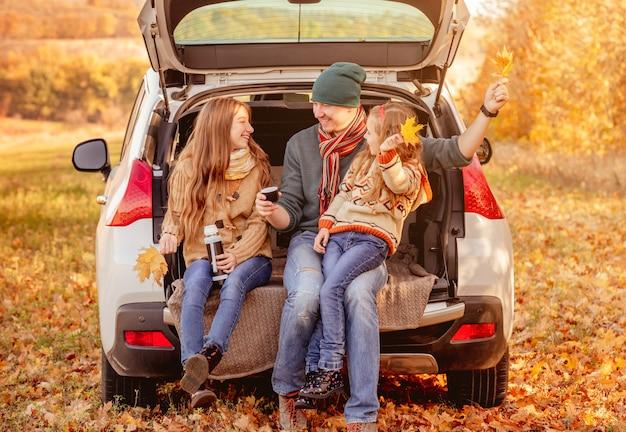 Padre con figlie in un ambiente autunnale