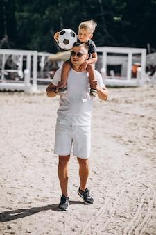 Padre con figlio a giocare a calcio in spiaggia