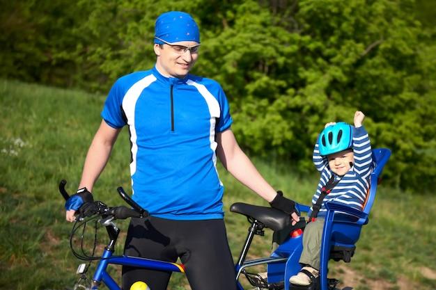 Padre con figlio in sedia per bicicletta