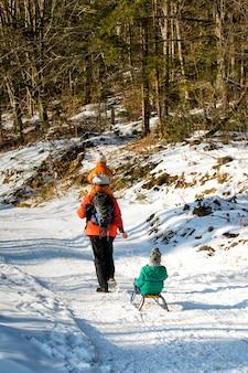 Padre con suo figlio sulle spalle porta il secondo figlio su una slitta sulla strada in un bosco innevato
