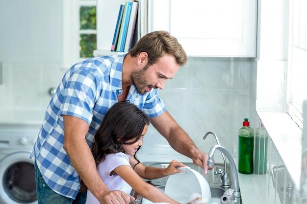 Padre d'aiuto della figlia nel lavaggio degli utensili