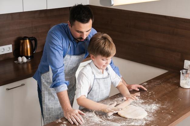 Padre d'angolo alto che insegna al figlio a rotolare pasta