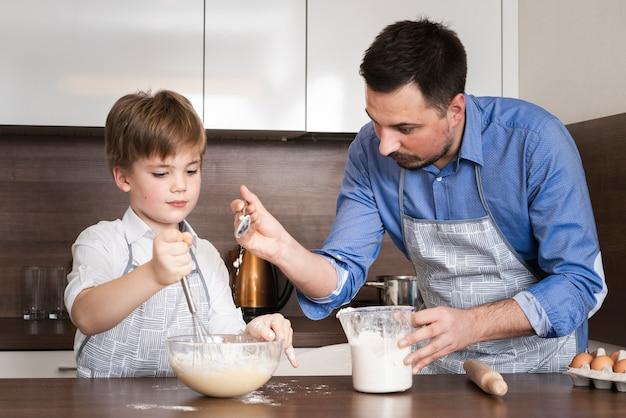 Padre d'angolo basso che insegna al figlio a produrre pasta