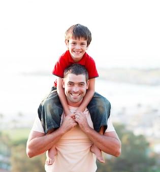 Padre dando figlio cavalluccio
