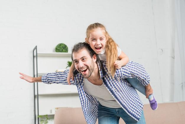 Padre dando un cavalluccio a sua figlia