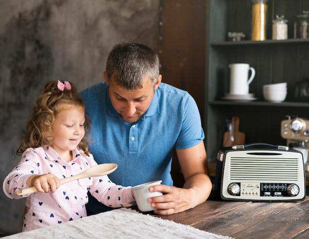 Padre del colpo medio che si siede con la figlia nella cucina