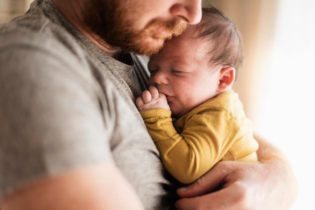 Padre del primo piano che abbraccia il suo bambino