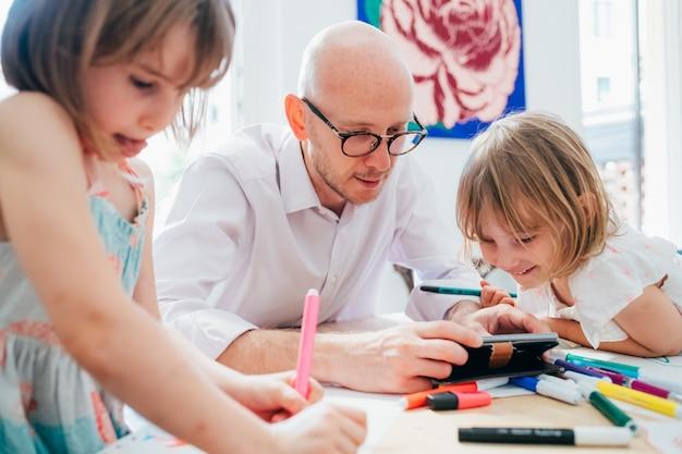 Padre di due bambine che studiano a casa al coperto