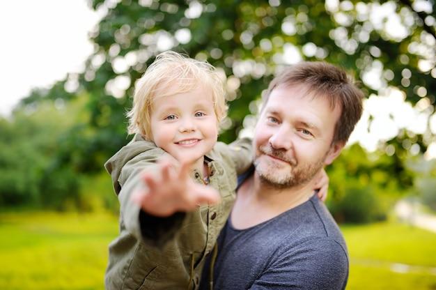 Padre di medio evo con il suo piccolo figlio divertendosi insieme all'aperto
