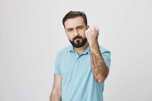 Padre di mezza età barbuto arrabbiato che rimprovera, agitando il pugno in minaccia