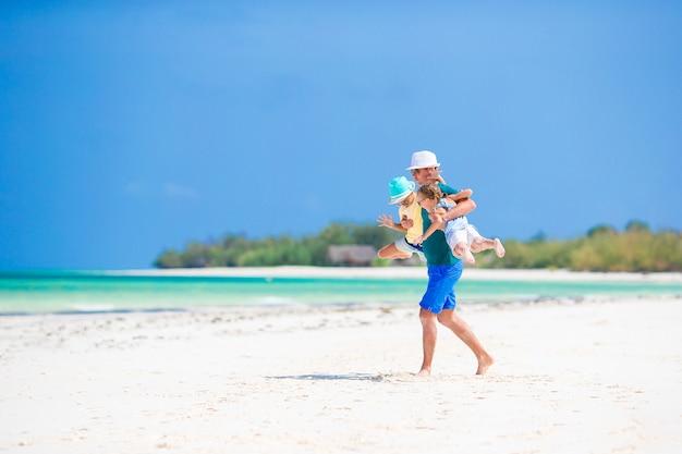 Padre e bambine si divertono molto sulla spiaggia di sabbia bianca
