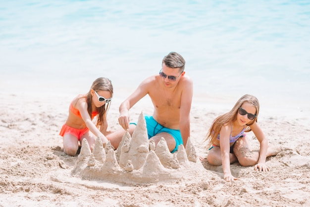 Padre e bambini che fanno il castello di sabbia alla spiaggia tropicale. famiglia che gioca con i giocattoli da spiaggia