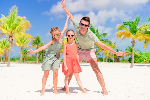Padre e bambini che godono le vacanze estive della spiaggia
