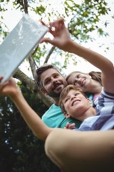 Padre e bambini che prendono un selfie con la compressa digitale