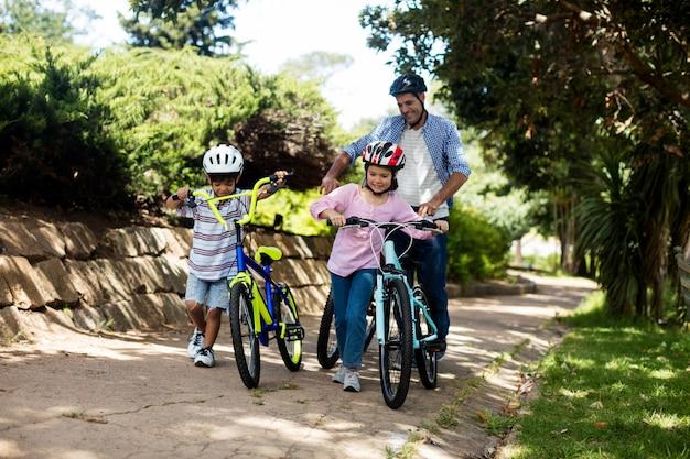 Padre e bambini che stanno con la bicicletta in parco