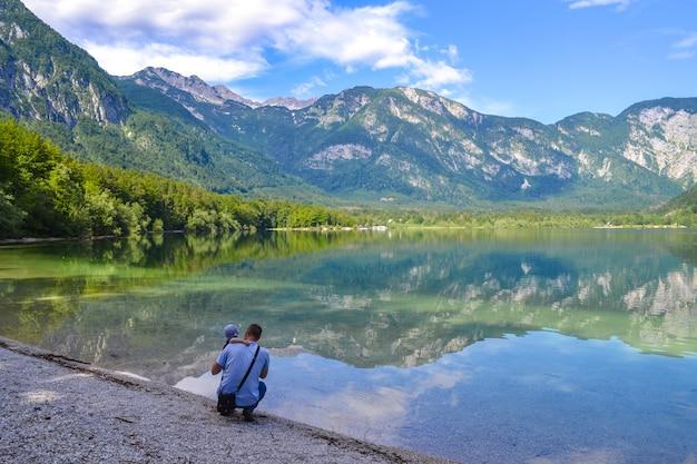 Padre e bambino ammirano il tranquillo lago di montagna in una luminosa giornata di sole. l'uomo abbraccia il figlio su una betulla di lago e guarda in lontananza.