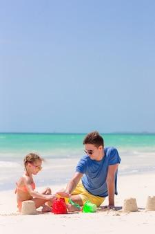 Padre e bambino che fanno il castello di sabbia in spiaggia tropicale