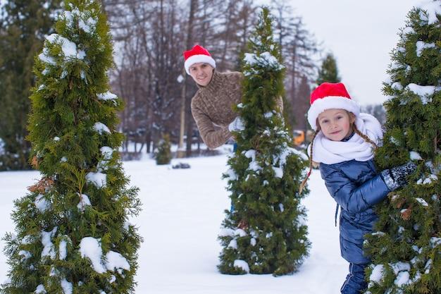 Padre e bambino felici in cappelli di santa con l'albero di natale all'aperto