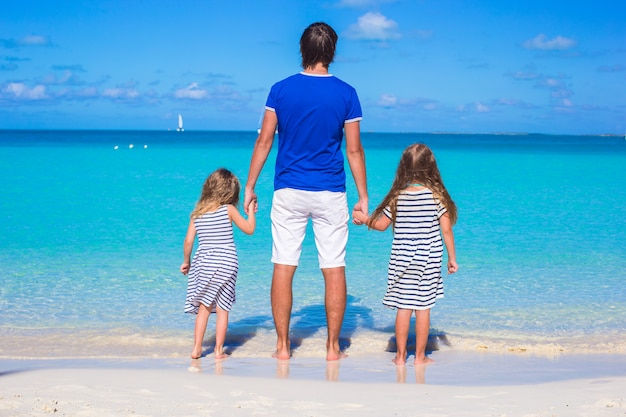 Padre e due figli che camminano vicino al mare