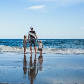 Padre e due figlie in piedi sulla spiaggia, mar mediterraneo