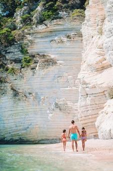 Padre e due figlie sulla spiaggia caraibica