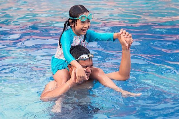 Padre e figlia asiatici che giocano nella piscina con la guida della ragazza sull'uomo.