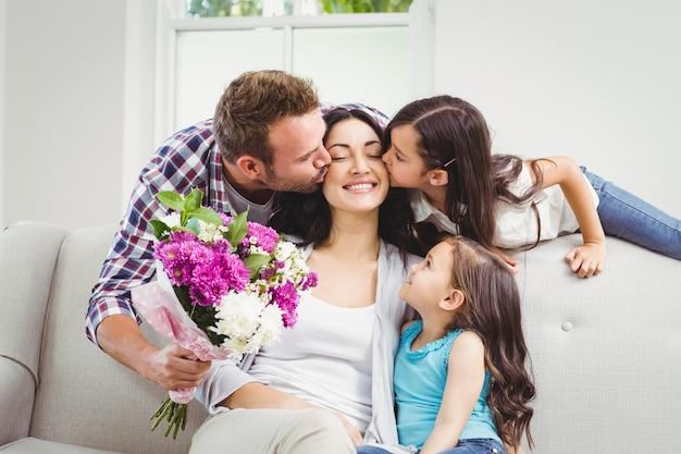 Padre e figlia che baciano madre seduta sul divano